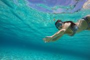 girl is snorkeling on the white stone beach